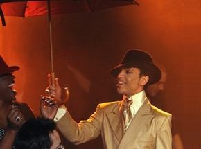 Someone smiling at Prince dressed in a gold metallic suit and carrying an umbrella