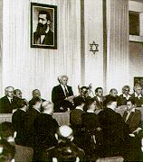 A man reads a document to a small audience assembled before him. Behind him are two elongated flags bearing the Star of David and portrait of a bearded man in his forties.