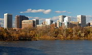 Numerous high-rise buildings rises over a dark river and its leafy autumnal shore.