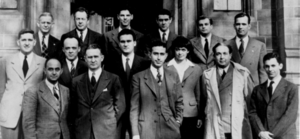 A group photo of 14 men in suits and 1 woman in three rows facing the vewier.