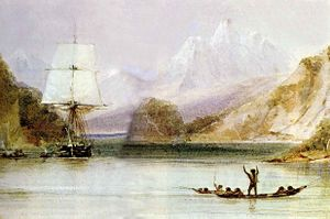 On a sea inlet surrounded by steep hills, with high snow covered mountains in the distance, someone standing in an open canoe waves at a square-rigged sailing ship, seen from the front