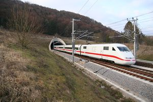 White electric train with red cheatline emerging from tunnel in the countryside