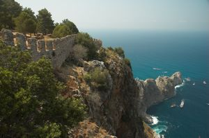 Blue-green sea surrounds a rocky peninsula covered by green trees and a stone castle wall with crenelations.