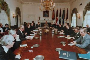 Thatcher is the only woman in a room, where a dozen men in suits sit around an oval table. Reagan and Thatcher sit opposite each other in the middle of the long axis of the table. The room is decorated in white, with drapes, a gold chandelier and a portrait of Lincoln.