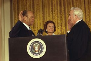 A man in a suit, his right hand in the air, stands next to his wife and speaks to another man in the robes of a judge. The group stands in front of a curtain, behind a podium bearing the seal of the President of the United States.