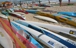 Photo more than a dozen kayaks lying next to each other on a beach