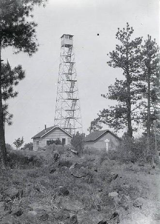 A four-legged tower with a small at the top, next to two one-story buildings. The tower is four stories tall. Trees are at either side, and in the foreground there are rocks, some vegetation, and a rough trail.