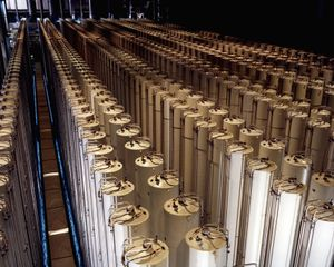 A photo of a large hall filled with arrays of long white standing cylinders.