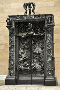 Ornate, bronze door panels and frame showing figures and scenes in relief.