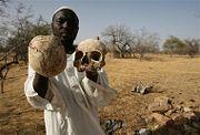 ابراهيم، أحد الناجين السودانين يقف بفي أحد ضواحي مكجار، السودان يحمل جماجم وبقايا عظام بشرية والتي تنتشر في أرجاء المدينة