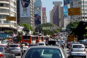Looking down a busy road, which is banked on both sides by tall buildings, some of which are covered in advertisement billboards