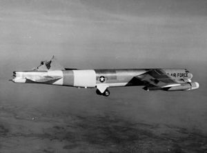 Black-and-white photo of a B-52 with its vertical stabilizer sheared off, but still flying.