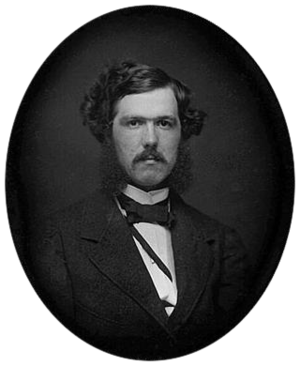 Black-and-white photograph of a young man with a mustache