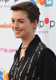 A short-haired brunette, wearing a black dress, is smiling to her left