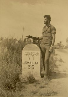A bearded soldier with an Uzi next to a road sign specifying the distance to Ismailia