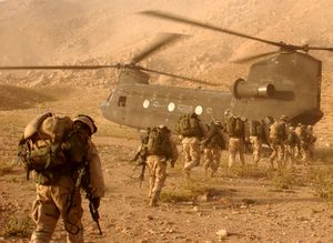 A line of soldiers carrying equipment on their backs walking toward a transport helicopter in desert terrain