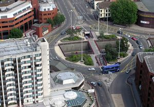Aerial view of roundabout, a junction of several streets. Vehicles traverse around the roundabout, which is surrounded by buildings, mostly multi-storey