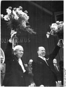 Two smiling men raise bouquets of flowers over their heads.