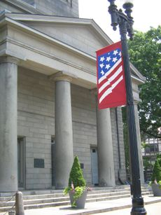 A tall, grey brick building with four columns before the entrance. In the foreground, a black lightpost is seen with a banner featuring a version of the flag of the United States.