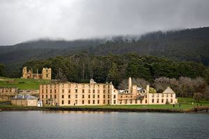 A calm body of water is in the foreground. The shoreline is about 200 metres away. To the left, close to the shore, are three tall gum trees; behind them on an incline are ruins, including walls and watchtowers of light-coloured stone and brick, what appear to be the foundations of walls, and grassed areas. To the right lie the outer walls of a large rectangular four-storey building dotted with regularly spaced windows. Forested land rises gently to a peak several kilometres back from the shore.