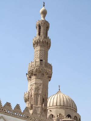 An ornate carved stone minaret, with a carved stone railing around three balconies, the first below its center, the second two thirds the way up, and the third near its top. The tip of the minaret is a large bulb-shaped stone decoration with a small bulb-shaped metal finial. Behind the minaret most of a dome is visible.