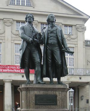 "Photograph of a large bronze statue of two men standing side-by-side and facing forward. The statue is on a stone pedestal, which has a plaque that reads ""Dem Dichterpaar/Goethe und Schiller/das Vaterland""."